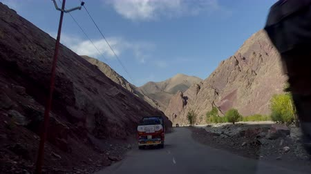 LADAKH, INDIA - SEPTEMBER 13, 2017: Camera follows tank truck driving on Leh–Manali Highway and carrying gasoline and passes by car and bikers riding motorcycles. Traffic on beautiful mountain road. Стоковые видеозаписи