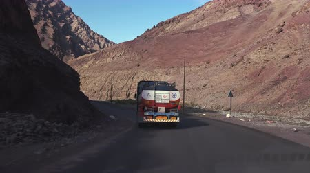 LADAKH, INDIA - SEPTEMBER 13, 2017: Camera follows gasoline tank truck driving on curvy Leh–Manali Highway. Van rides on bent switchback road flanked by picturesque rocky mountains, back view.