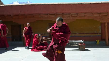gompa : LIKIR, INDIA - SEPTEMBER 18, 2017: Buddhist monks rehearse Cham Dance in courtyard of main temple of Likir Gompa monastery against other monastics playing dungchen or Tibetan horn on background. Stock Footage
