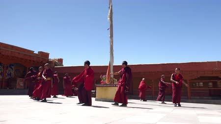 himalája : LIKIR, INDIA - SEPTEMBER 18, 2017: Cham Dance rehearsal in courtyard of main temple of Likir Gompa monastery. Buddhist monks wearing long robes rehearse steps of traditional ritual performance.