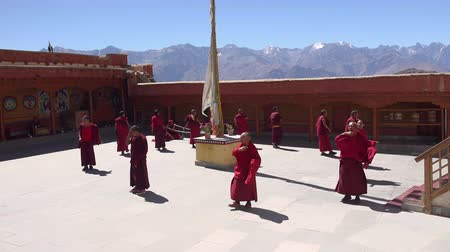 LIKIR, INDIA - SEPTEMBER 18, 2017: Buddhist monks dancing to sound of Tibetan horns in courtyard of main temple of Likir Gompa monastery against spectacular Himalaya mountain range on background. Stok Video