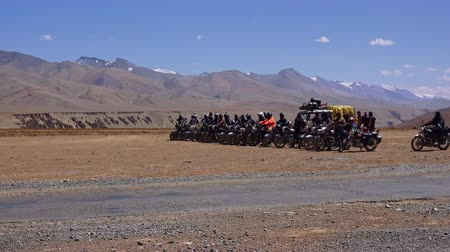 himaláje : Indian bikers standing on starting line and waiting for race against Himalaya mountains and blue sky on background. Motorcycle riders on Leh-Manali Highway. More plains, Ladakh region, India.