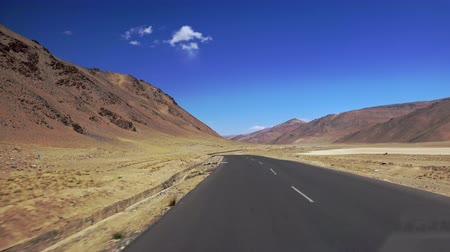 flanked : Camera moves along Leh-Manali Highway crossing More plains and flanked by Himalaya mountain range. View on amazing mountainous scenery from car driving along road on sunny day. Ladakh, India Stock Footage