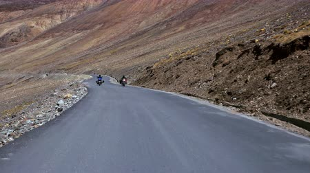 Spectacular scene with bikers riding motorcycles on Leh-Manali Highway flanked by rocky slopes of Himalaya mountains. Camera moves along road and passes by motorcyclists on bikes. Ladakh, India. Стоковые видеозаписи