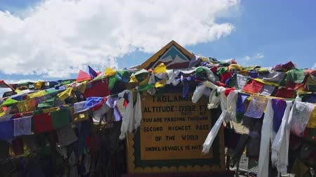 himalája : Bright colored Buddhist ragged prayer flag garlands hung on altitude sign on Taglang La high mountain pass and waving in wind against blue sunny sky. Manali-Leh highway, Ladakh. India. Camera zooms