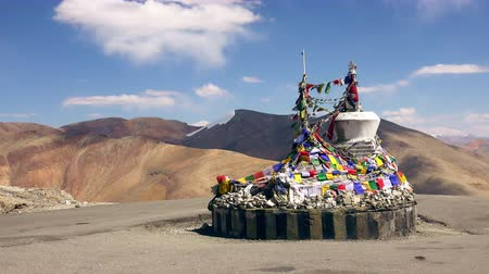 Buddhist stupa decorated by bright colored prayer flags waving in wind against high Himalaya mountains. Place for religious offerings at Taglang La mountain pass. Manali-Leh highway, Ladakh. India