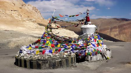himalája : Buddhist stupa decorated by bright colored prayer flags waving in wind against high Himalaya mountains. Place for religious offerings at Taglang La mountain pass. Manali-Leh highway, Ladakh. India