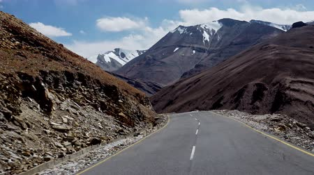 Camera moves along switchbacks of bent Leh–Manali Highway flanked by amazing Himalaya mountains on sunny day. Journey on winding road against mountainous terrain. Ladakh, India. Accelerated video. Стоковые видеозаписи