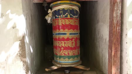 Buddhist Prayer or Mani wheel decorated with Sanskrit symbols spins and rings bell. Ornate rotating traditional cylinder with text of mantra written on it for religious pray. Ladakh. Video with sound.
