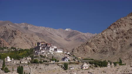 Picturesque view of Likir Gompa Buddhist monastery situated in valley flanked by beautiful Himalaya mountains. Gorgeous mountainous landscape with religious buildings. Ladakh, India. Camera zooms out.