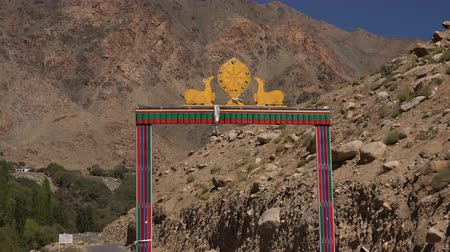 Gates of Likir Gompa Buddhist monastery decorated with Dharmachakra or wheel of Dharma flanked by pair of deers against picturesque rocky mountains and clear blue sky. Ladakh, India. Camera zooms out. Стоковые видеозаписи