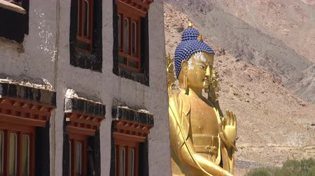 gompa : Large golden statue of Buddha Maitreya sitting in Dharmachakra Mudra beside ancient building of Likir Gompa Buddhist monastery against rocky mountain slope and sky. Ladakh, India. Camera zooms out.