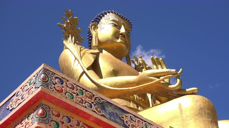 likir gompa : Beautiful golden statue of Buddha Maitreya sitting in Dharmachakra Mudra and holding lotus flower in hand against blue sky. Traditional ancient Buddhist sculpture. Ladakh, India. Camera zooms out. Stock Footage