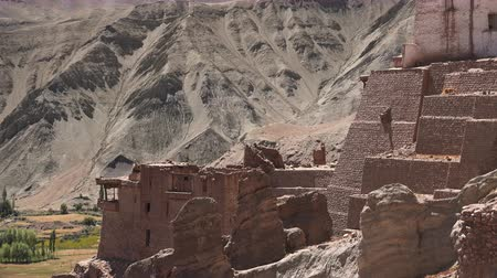 Ruins of Basgo Palace beside Bazgo Gompa monastery against gorgeous mountainous terrain illuminated by sunlight and clear blue sky. Remains of ancient building. Ladakh, India. Camera zooms out.