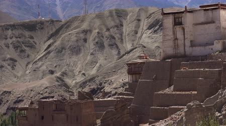 tibet : Spectacular view of ancient Basgo monastery situated on rocky cliff or hill against beautiful Himalaya mountain range. Bazgo Gompa buildings on clear sunny day. Ladakh, India. Camera zooms out.