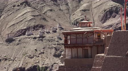 Ancient building of Basgo buddhist monastery or Bazgo Gompa with pointed roof and gallery or balcony decorated with prayer flag garlands fluttering in wind against rocky mountain slope. Ladakh., India