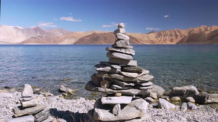 Traditional Buddhist stone pyramid or rock tower against clear water of Pangong Tso lake, Himalaya mountains and blue sky. Concept of serenity, meditation and zen. Ladakh, India. Panoramic view. Стоковые видеозаписи