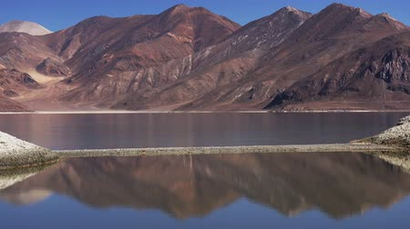 Peaceful landscape with beautiful Himalaya mountains reflecting in tranquil water of Pangong Tso lake, Ladakh, India. Gorgeous mountainous terrain, picturesque meditative scenery. Camera stays still.