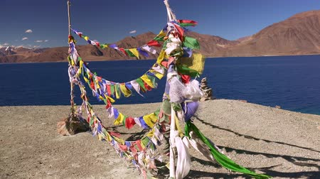 Traditional Buddhist prayer flag garlands fluttering in wind and stone pyramid against Pangong Tso lake and Himalaya mountain range. Beautiful sacred place for pray and meditation. Ladakh, India