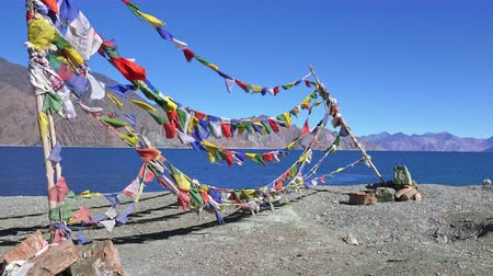tibet : Spectacular scenery with colorful Buddhist prayer flag garlands waiving in wind against Pangong Tso lake and Himalaya mountains. Sacred religious place surrounded by mountainous terrain. Ladakh, India