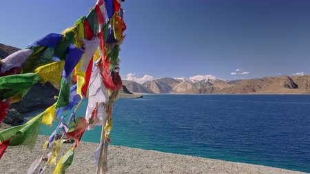 Beautiful landscape with colorful traditional Buddhist prayer flags fluttering in wind against Pangong Tso lake and gorgeous Himalaya mountains. Picturesque tranquil meditative scenery. Ladakh, India