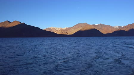 Spectacular landscape with Pangong Tso lake and gorgeous Himalayan mountain range illuminated by soft light of setting sun. Picturesque sunset or beautiful sundown. Ladakh, India. Panoramic view.