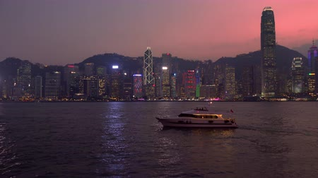 HONG KONG - OCT 23, 2017: Yacht swaying on waves against gorgeous night cityscape with illuminated skyscrapers on background. Victoria harbor, Hong Kong