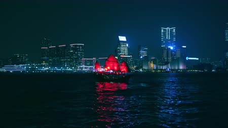 HONG KONG - OCT 26, 2017: Traditional ancient Chinese cruise sailboat or junk with red sails departs from Hing Kong pier and crosses Victoria harbor against beautiful night cityscape on background.