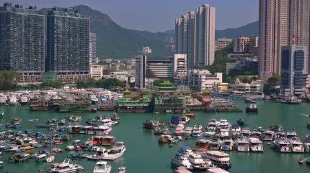 HONG KONG - OCT 27, 2017: Boats and yachts swaying on waves against cityscape on background. Floating village. Historical place and popular touristic landmark. Aberdeen harbor, Hong Kong. Zooming out Стоковые видеозаписи