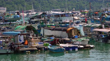 HONG KONG - OCT 27, 2017: Boats and yachts swaying on waves. Floating village. Historical place and popular touristic landmark. Aberdeen harbor, Hong Kong.