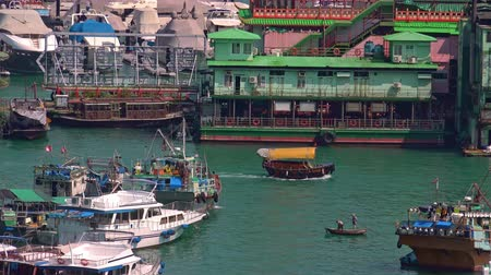 HONG KONG - OCT 27, 2017: Wooden boat passes by historical floating village, community living on traditional junks or ancient Chinese sailboats and Jumbo restaurant. Aberdeen harbor, Hong Kong.