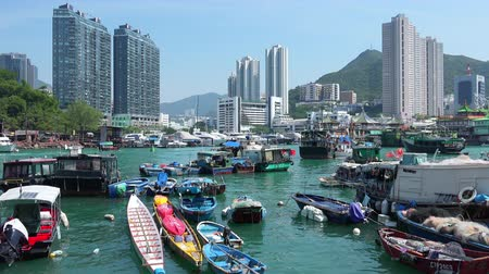 HONG KONG - OCT 27, 2017: Boats and yachts swaying on waves against gorgeous cityscape on background. Floating village. Historical place and popular touristic landmark. Aberdeen harbor, Hong Kong.