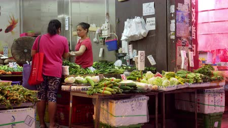 HONG KONG - OCT 29, 2017: People  shopping green vegetables at street shop. Greengrocer selling food at traditional Asian open market. Local retail trade.