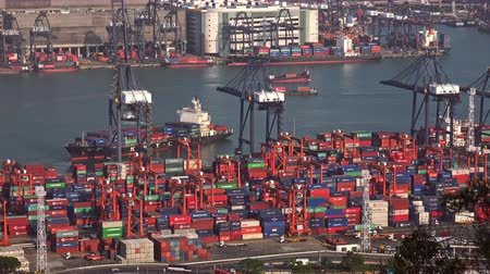 HONG KONG - NOV 1, 2017: Aerial view of freighter ships or vessels loaded with containers passing by seaport or marine cargo terminal with loader cranes. Maritime transportation at busy sea port.
