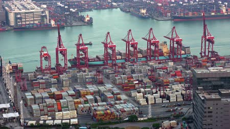 HONG KONG - NOV 1, 2017: Bird eye view of marine cargo terminal. Ships passing by seaport, stacks of containers and moving loader cranes. Work of busy sea port during daytime. Fast speed video.