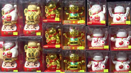 HONG KONG - NOV 2, 2017: Small figures or statues of beckoning or lucky cat with moving upright paws in plastic packaging displayed in shop or store window. Traditional Chinese symbol of good luck.