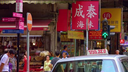 sell : HONG KONG - NOV 4, 2017: Traditional shops or convenience stores selling local goods with lots of signboards, crowds of people, traffic lights and driving taxi cabs on modern Asian city street. Stock Footage
