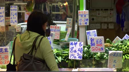 hieroglifa : HONG KONG - NOV 4, 2017: Female buyer standing beside counter with green vegetables and looking at price tags. Greengrocers shop selling food at traditional Asian open market. Local retail trade. Stock mozgókép