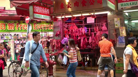 HONG KONG - NOV 4, 2017: butcher shop or store with hanging cuts of meat on sale at traditional Asian street market, man washing asphalt with hosepipe in front of it and people passing by camera. Стоковые видеозаписи