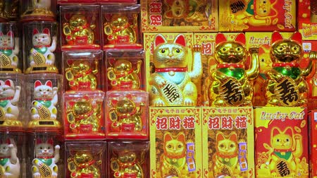 beckoning : HONG KONG - NOV 2, 2017: Small figures or statues of beckoning or lucky cat with moving upright paws in plastic packaging displayed in shop or store window. Traditional Chinese symbol of good luck.