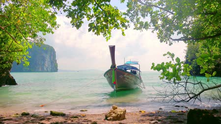 KRABI, THAILAND - DEC 8, 2017: Traditional Thai long-tail wooden boat with ribbon decoration moored to shore with trees and slightly swaying on sea waves against beautiful seascape on background.
