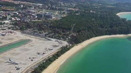PHUKET, THAILAND - NOV 18, 2017: departure from Phuket international airport. Flight above runway, terminal buildings, landed aircrafts and coast washed by sea. View from flying ascending airplane. Стоковые видеозаписи