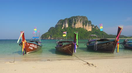 KRABI, THAILAND - DEC 9, 2017: Thai traditional wooden long-tail boats moored to sandy shore and slightly swaying on sea waves against large rocky cliff and clear blue sky. Railay Beach, Thailand Стоковые видеозаписи