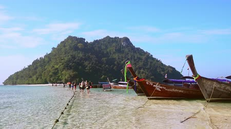 KRABI, THAILAND - DEC 9, 2017: Boat tour to Koh Tub and Koh Mor islands. Thai long-tail vessels moored to shore and people walking along coastline against limestone rock formation on background.