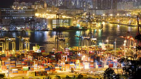 HONG KONG - NOV 1, 2017: View of marine cargo terminal at night. Ships passing by seaport, stacks of containers and moving loader cranes. Work of busy sea port during nighttime. Time lapse video.