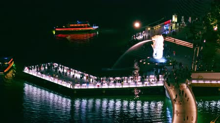 SINGAPORE - OCT 19, 2017: Night view of Merlion statue with water stream pouring from its mouth standing on illuminated pier with walking people and pleasure boats passing by. Fast motion video