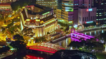 SINGAPORE - OCT 19, 2017: Building of Fullerton hotel, Cavenagh and Anderson Bridges lit up at night. Beautiful aerial view of historical city center in evening. Gorgeous cityscape or urban landscape.