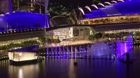 SINGAPORE - OCT 19, 2017: Spectacular daily light show in front of Marina Bay Sands Hotel and Shopping Mall. Beautiful view of tall fountain water streams glowing in darkness. Fast motion video.