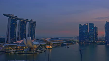 SINGAPORE - OCT 20, 2017: Stunning scenery with shift from evening to night or nightfall, futuristic buildings of Marina Bay Sands hotel and ArtScience Museum and skyscrapers. Fast motion video. Стоковые видеозаписи