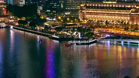 SINGAPORE - OCT 20, 2017: Beautiful night scenery with pleasure boats sailing by Merlion statue standing against The Fullerton Hotel and Marina Bay Financial Centre on background. Camera zooms out . Стоковые видеозаписи